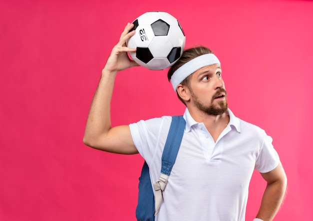 Impressed young handsome sporty man wearing headband and wristbands with back bag on shoulder looking at side holding soccer ball on head isolated on pink wall
