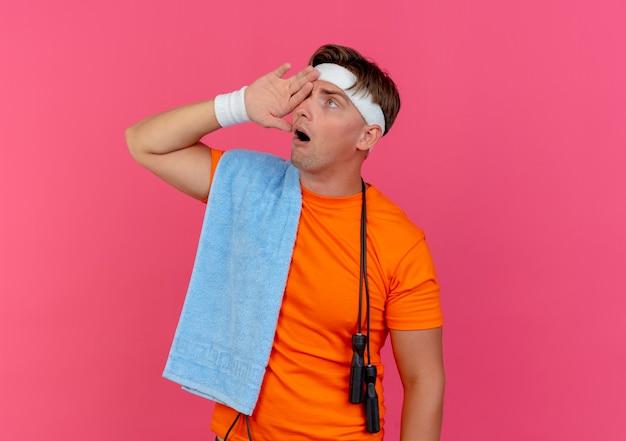 Impressionato giovane uomo sportivo bello che indossa fascia e braccialetti con asciugamano e corda per saltare intorno al collo mettendo la mano sull'occhio guardando il lato isolato sul rosa