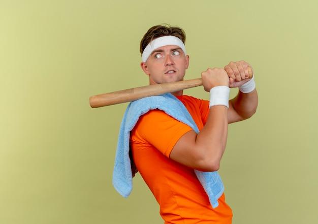 Impressionato giovane uomo sportivo bello che indossa fascia e braccialetti con asciugamano sulla spalla in piedi in vista di profilo tenendo la mazza da baseball sulla spalla guardando dietro