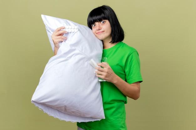 Impressionato giovane ragazza caucasica malata tenendo il cuscino confezione di compresse e bicchiere d'acqua che guarda l'obbiettivo isolato su sfondo verde oliva con lo spazio della copia