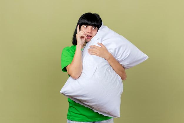 Impressionato giovane ragazza caucasica malata abbracciando cuscino guardando lato alzando il dito isolato su sfondo verde oliva con lo spazio della copia