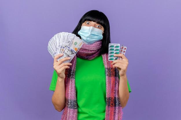 복사 공간 보라색 배경에 고립 된 카메라를 찾고 돈과 캡슐의 팩을 들고 마스크와 스카프를 착용하는 젊은 아픈 백인 소녀 감동