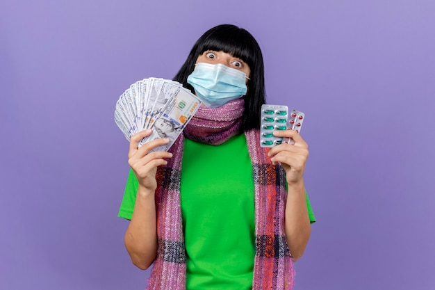 Impressed young ill caucasian girl wearing mask and scarf holding money and packs of capsules looking at camera isolated on purple background with copy space