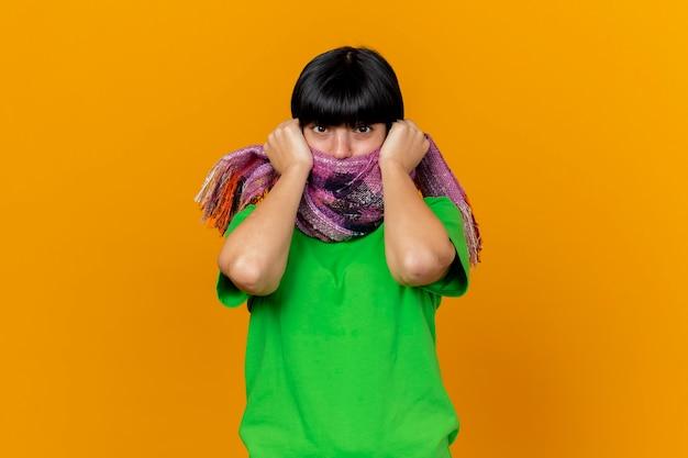 Impressionato giovane ragazza caucasica malata che indossa sciarpa che copre la bocca con sciarpa afferrando sciarpa isolata sulla parete arancione con lo spazio della copia