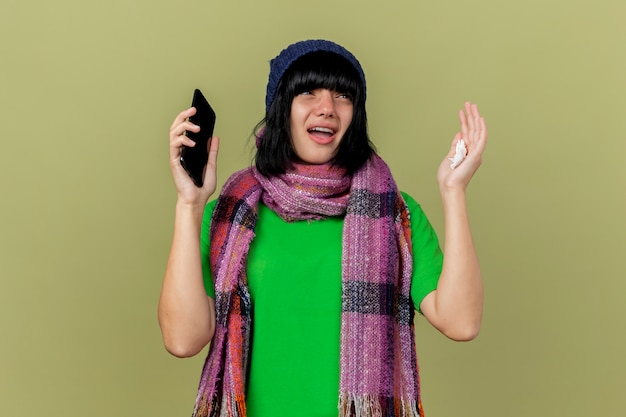 Impressionato giovane ragazza caucasica malata che indossa cappello invernale e sciarpa tenendo il telefono cellulare e il tovagliolo guardando il lato alzando la mano isolata su sfondo verde oliva con spazio di copia