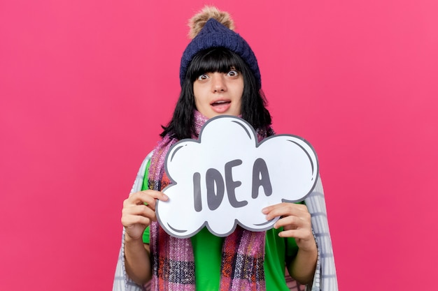 Impressed young ill caucasian girl wearing winter hat and scarf wrapped in plaid holding idea bubble  isolated on crimson wall with copy space