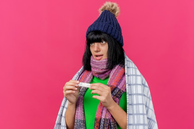 Impressed young ill caucasian girl wearing winter hat and scarf wrapped in plaid holding medical plaster looking straight isolated on crimson background with copy space