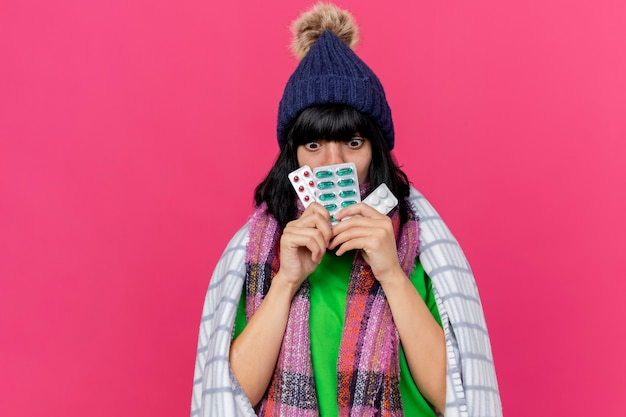 Impressionato giovane ragazza caucasica malata che indossa cappello invernale e sciarpa avvolta in plaid che tiene confezioni di pillole mediche davanti alla bocca guardando verso il basso isolato su sfondo cremisi con lo spazio della copia