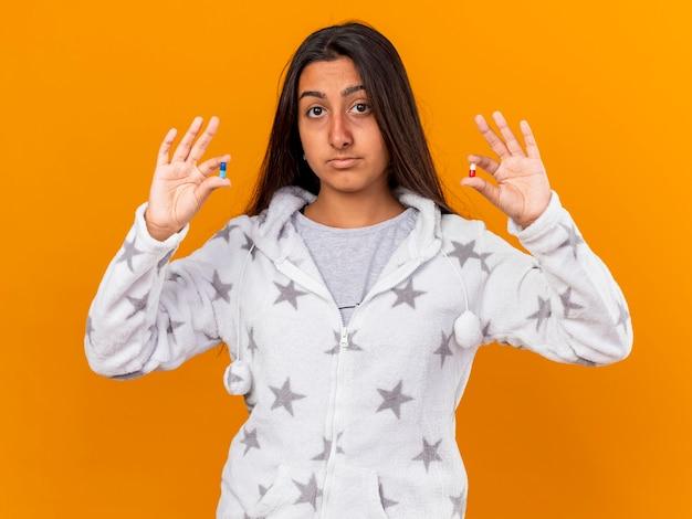 Impressionato giovane ragazza malata che guarda l'obbiettivo azienda pillole isolate su sfondo giallo