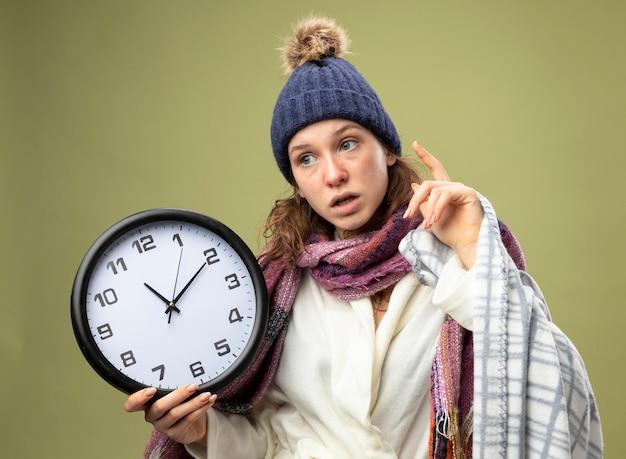 Impressionato giovane ragazza malata guardando al lato che indossa una tunica bianca e cappello invernale con sciarpa che tiene l'orologio da parete avvolto in punti plaid in alto isolato su verde oliva