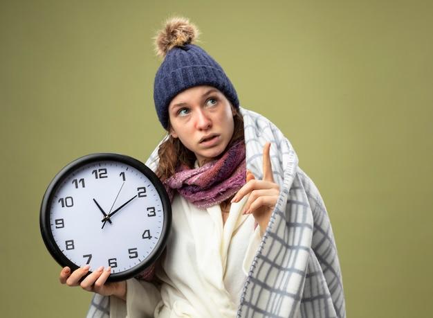 Впечатленная молодая больная девушка, смотрящая вверх в белом халате и зимней шапке с шарфом, держит настенные часы, завернутые в клетчатые очки