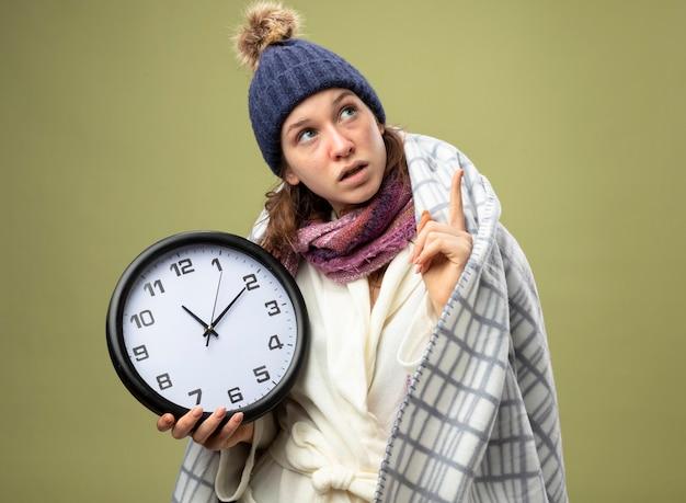 Impressionato giovane ragazza malata che indossa una tunica bianca e cappello invernale con sciarpa tenendo l'orologio da parete avvolto in punti plaid in alto isolato su verde oliva