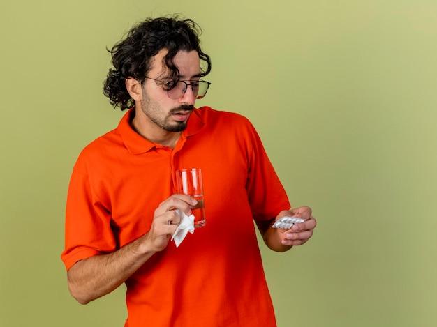 Impressionato giovane uomo malato con gli occhiali che tiene un bicchiere di acqua confezione di compresse e tovagliolo guardando compresse isolate sulla parete verde oliva con spazio di copia