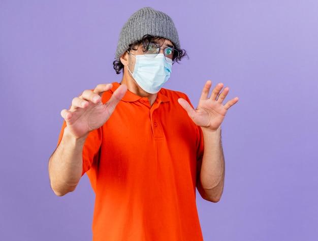 コピースペースのある紫色の壁に隔離された空気の中で手を保ちながら正面を見て眼鏡マスクと冬の帽子を身に着けている感動の若い病気の男