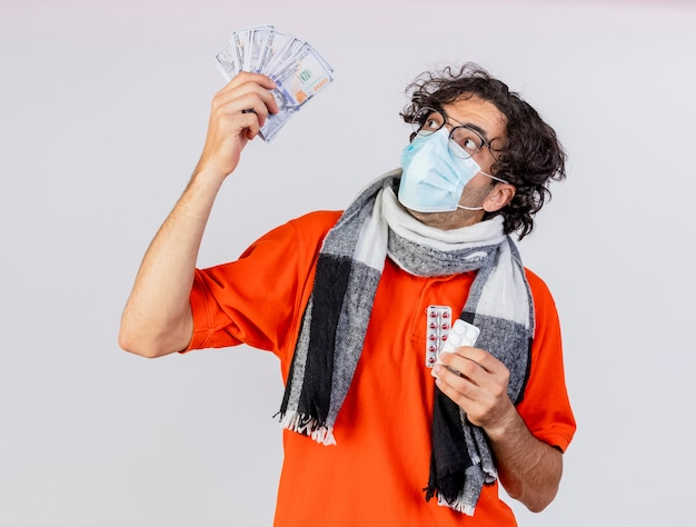 Impressed young ill man wearing glasses scarf and mask holding money and pills looking at money isolated on white wall