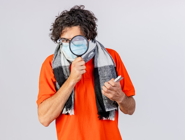 Impressed young ill man wearing glasses scarf and mask holding packs of medical pills looking at them through magnifying glass isolated on white wall