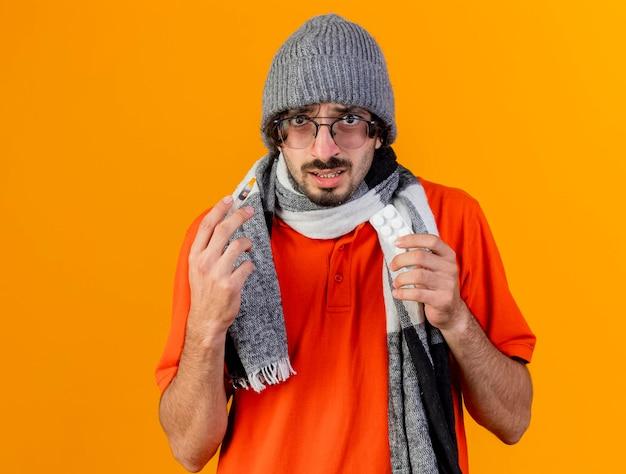 안경 겨울 모자와 스카프 들고 주사기와 복사 공간 오렌지 벽에 고립 된 전면을보고 의료 정제 팩을 입고 감동 젊은 아픈 남자