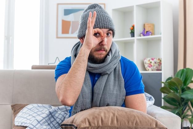 표정 제스처를하고 카메라를보고 그의 다리에 베개와 함께 거실에서 소파에 앉아 스카프와 겨울 모자를 쓰고 감동 젊은 아픈 남자
