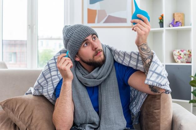 Impressionato giovane uomo malato che indossa sciarpa e cappello invernale seduto sul divano nel soggiorno avvolto in una coperta tenendo clisteri sollevando uno guardandolo