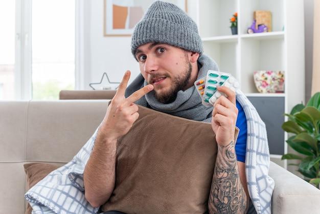 Impressionato giovane uomo malato che indossa sciarpa e cappello invernale avvolto in una coperta seduto sul divano in soggiorno tenendo il cuscino guardando la telecamera che mostra confezioni di pillole e mostrando due con la mano