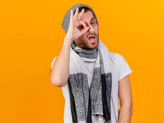 冬の帽子と黄色の背景で隔離の外観ジェスチャーを示すスカーフを身に着けている印象的な若い病気の男