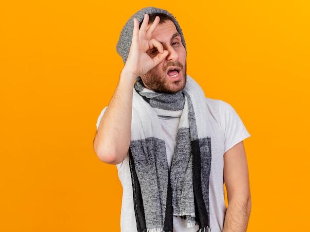 Impressionato giovane uomo malato che indossa cappello invernale e sciarpa che mostra gesto di sguardo isolato su sfondo giallo