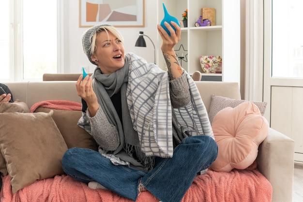 Impressionato giovane malata donna slava con sciarpa intorno al collo avvolto in plaid indossando cappello invernale tenendo e guardando clisteri seduto sul divano in soggiorno