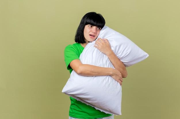Impressionato giovane donna malata che abbraccia il cuscino guardando il lato isolato sulla parete verde oliva