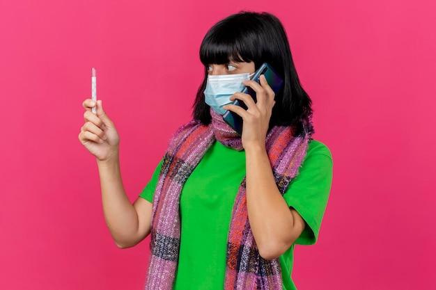 Впечатленная молодая больная женщина в маске и шарфе, держащая и смотрящая на термометр, разговаривает по телефону, изолированную на розовой стене с копией пространства