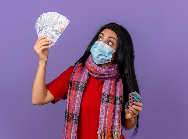 보라색 벽에 고립 된 돈을보고 돈과 캡슐의 팩을 들고 마스크와 스카프를 착용하는 젊은 아픈 여자를 감동