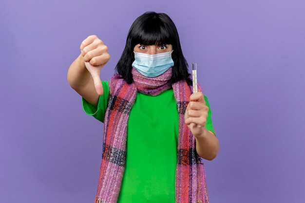 コピースペースと紫色の壁に分離された親指を下に示して正面を見て温度計を保持しているマスクとスカーフを身に着けている感銘を受けた若い病気の女性
