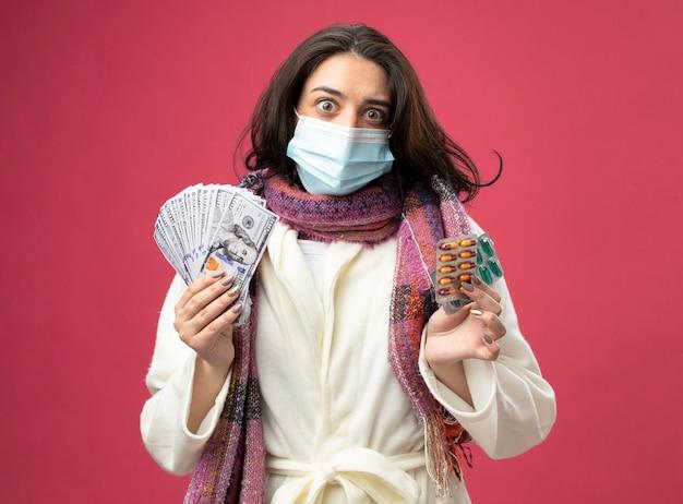 ピンクの壁に隔離された正面を見てお金と医療カプセルのパックを保持しているマスクとローブとスカーフを身に着けている感動の若い病気の女性