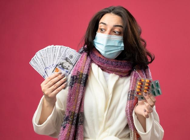 ピンクの壁に隔離されたお金を見てお金と医療カプセルのパックを保持しているマスクでローブとスカーフを身に着けている感銘を受けた若い病気の女性