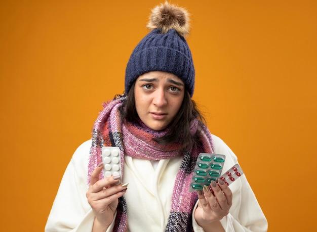 オレンジ色の壁に隔離された正面を見て、ローブの冬の帽子と医療薬のパックを保持しているスカーフを身に着けている感銘を受けた若い病気の女性