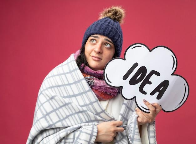 ピンクの壁に隔離された見上げるアイデアバブルを保持している格子縞に包まれたローブの冬の帽子とスカーフを身に着けている感動の若い病気の女性