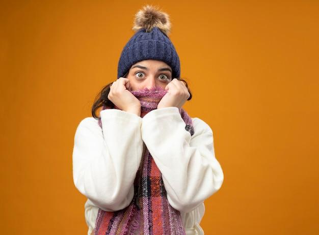 Impressionato giovane donna malata che indossa un abito invernale cappello e sciarpa guardando la bocca della copertura anteriore con sciarpa isolata sulla parete arancione