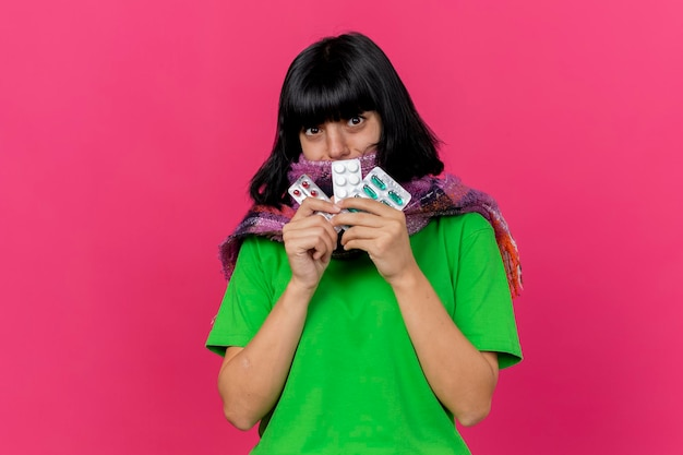Impressed young ill woman wearing scarf holding medical pills looking at front isolated on pink wall with copy space