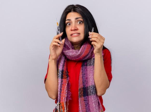 Sciarpa da portare della giovane donna ammalata impressionata che tiene la siringa e la fiala che esamina la parte anteriore isolata sulla parete bianca