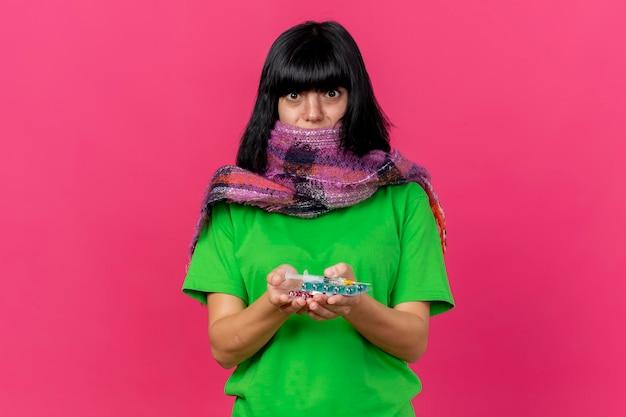 Sciarpa da portare della giovane donna ammalata impressionata che tiene siringa e pillole mediche che esaminano parte anteriore isolata sulla parete rosa con lo spazio della copia