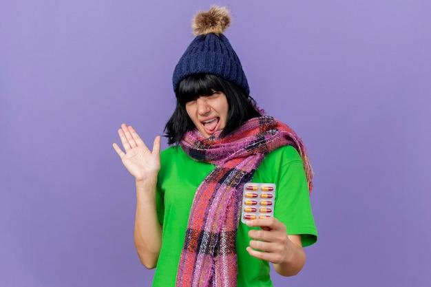 Impressionato giovane donna malata che indossa un cappello invernale e sciarpa che tiene il pacchetto di capsule guardando la parte anteriore che mostra la mano vuota isolata sulla parete viola con spazio di copia