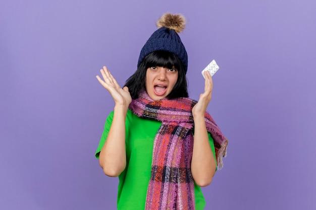 Impressionato giovane donna malata che indossa un cappello invernale e sciarpa che tiene il pacchetto di compresse che mostra la mano vuota guardando davanti isolato sulla parete viola con spazio di copia