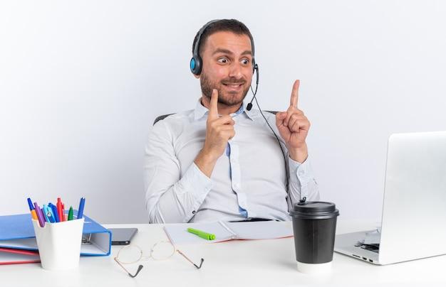 Impressionato giovane operatore di call center maschio che indossa l'auricolare seduto al tavolo con strumenti da ufficio guardando i punti del laptop in alto isolati sul muro bianco
