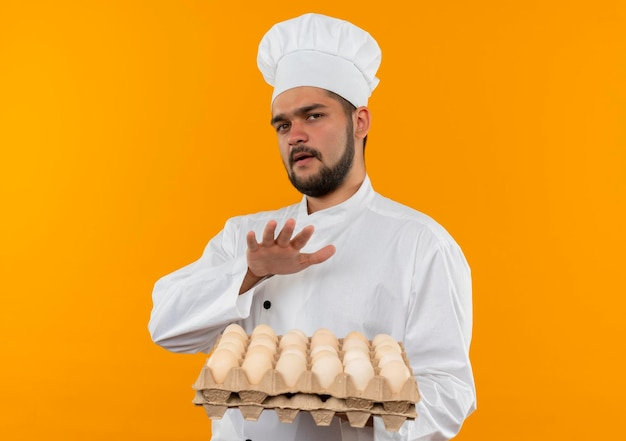 Impressed young male cook in chef uniform holding carton of eggs keeping hand above them isolated on orange wall