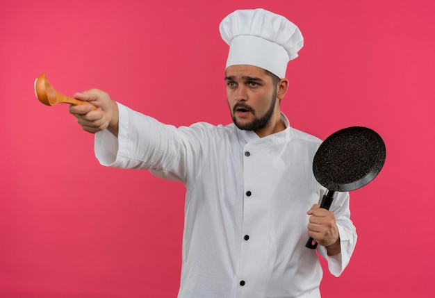 Impressionato giovane cuoco maschio in uniforme da chef che tiene in mano una padella e allunga il cucchiaio e guarda il lato isolato sulla parete rosa