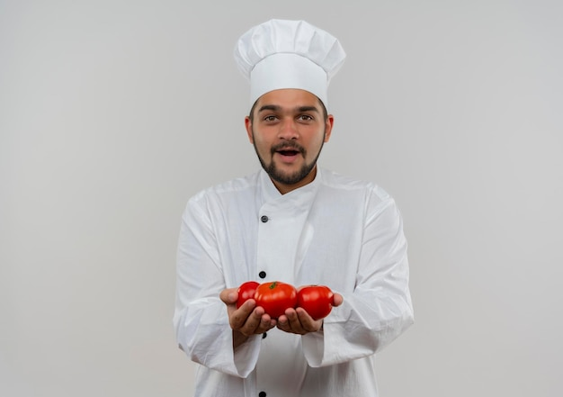 Impressed young male cook in chef uniform holding tomatoes isolated on white wall with copy space