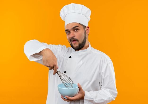 Impressionato giovane cuoco maschio in uniforme da chef che tiene in mano una frusta e una ciotola isolate sulla parete arancione orange