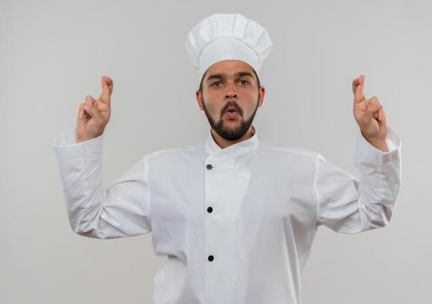 흰 벽에 고립 된 교차 손가락 제스처를 하 고 요리사 유니폼에 감동 된 젊은 남성 요리사