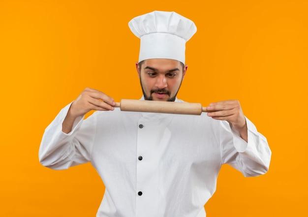 オレンジ色の壁に分離された麺棒を保持し、見るシェフの制服を着た若い男性料理人に感銘