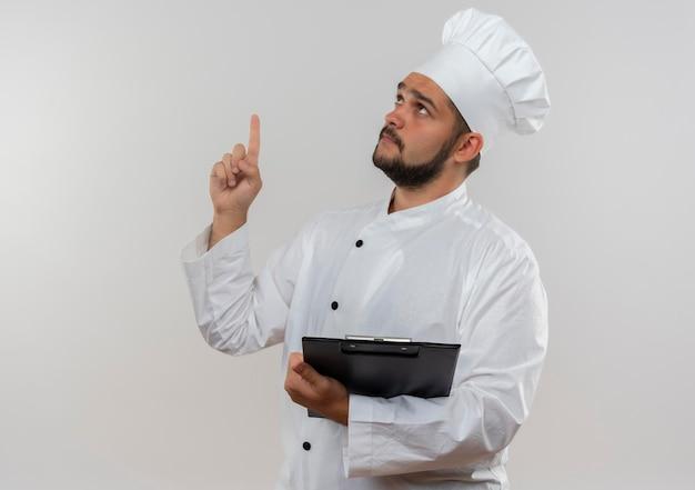 コピー スペースを持つ白い壁に分離されたクリップボードを見て、上向きを保持しているシェフの制服を着た感銘を受けた若い男性料理人