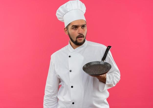 シェフの制服を着た印象的な若い男性料理人がフライパンを持ち、コピースペースのあるピンクの壁に隔離された側を見る